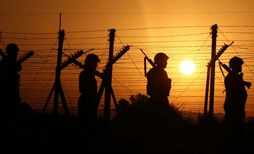 Indian soldiers silhouetted against the border