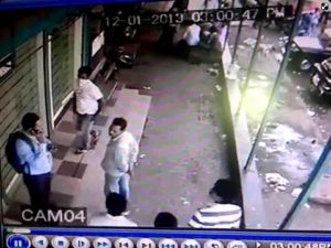 CCTV Screen grab 2 - Assailants gathering around the shop - one with handkerchief tied on face, another with stick held behind his back