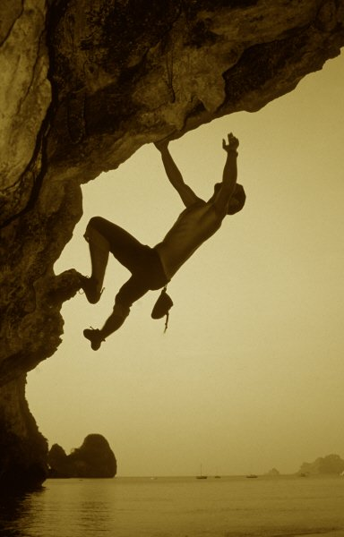 silhouette of a solo climber free climbing an overhang