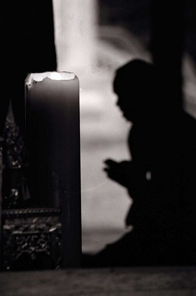 backlit silhouette of a monk praying