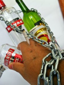 chain around bottles of alcohol and a hand
