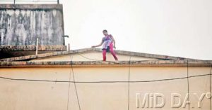 woman walking on building parapet
